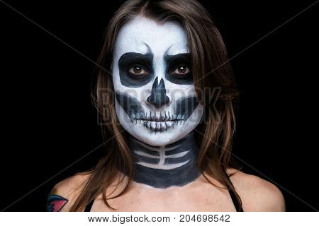 close up portrait of woman with Halloween skull make up over black background.