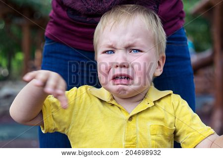 Little boy in a yellow T-shirt is badly upset and crying. Tears on her cheek