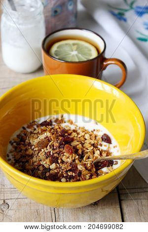 Homemade granola with yogurt and tea with lemon. Useful breakfast. Rustic style, selective focus.