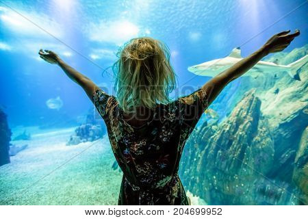 Happy caucasian blonde woman with open arms looking at fishes and shark in oceanarium. Female tourist enjoying in ocean exhibit tank. Lisbon, Portugal. Tourism, holidays, lifestyle and leisure concept