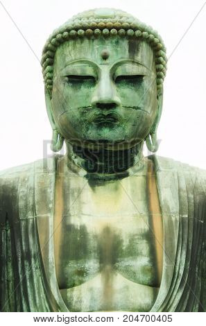 The Great Buddah of kamakura against a mostly white sky.