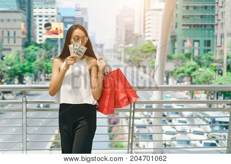business and modern lifestyle concept: Beautiful young woman holding red bag with hands and cash money shopping summer sale and fashion.