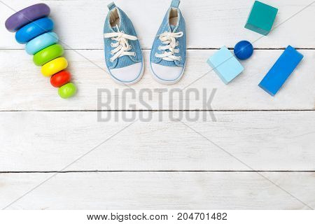 Shoes for little boy and wooden cubes on a wooden background