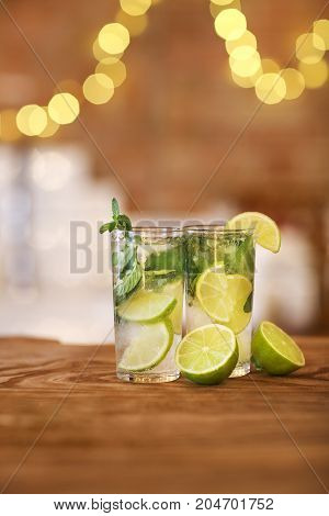 Two cocktail glasses with lime and mint on wooden bar counter