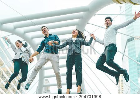 Successful business team shook hands together and jumping in the city Highly successful startup team concept of business and modern lifestyle.
