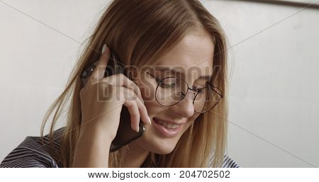 blonde woman's portrait talking on mobile smartphone closep. office style