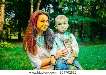 mother with son in holi paints in city park portraits