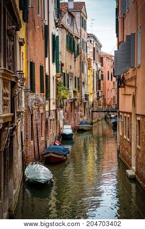 The old narrow street with a boats in Venice, Italy. Traditional Venetian street is a water canal. Boats are the main transport in Venice.