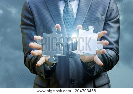 Hands Of The Businessman Connects Two Of The Puzzle .