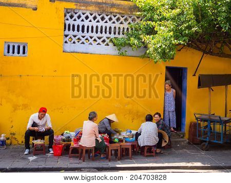 Hoian, Vietnam - August 05, 2017: Unidentified people sitting at outside of an old yellow house in Hoi An ancient town, UNESCO world heritage. Hoi An is one of the most popular destinations in Vietnam.