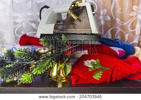 Winter clothes woolen socks Christmas tree branches and the iron on the top