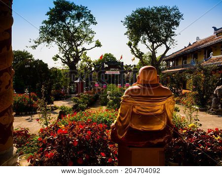 HOIAN, VIETNAM, SEPTEMBER, 04 2017: Back view of a budha in an ancient temple with a beautiful jarden with colorful flowers at hoian, in a sunny day in Vietnam.