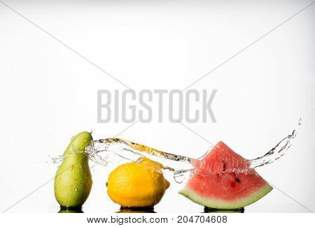 Watermelon With lemon and pear and water Splash isolated on white background.