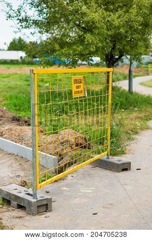 Yellow metal grid barrier with sign warning for construction by a new footpath on August 2017 in Poznan Poland