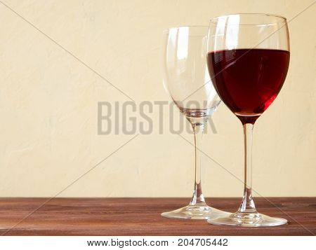 Glasses of red wine on the wooden table. Side view