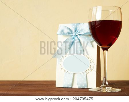 Glass of red wine on the wooden table. Side view