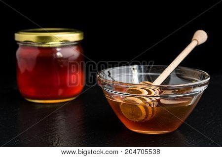 Honey in glass bowl and jar with wooden honey dipper on black background