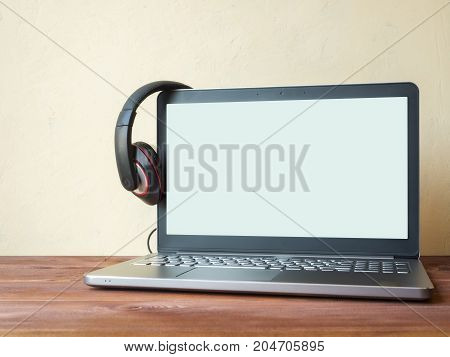 Laptop with blank screen on the wooden table