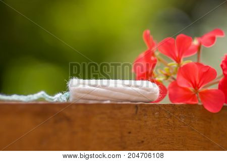 Feminine hygiene product - menstruation cotton tampon over a wooden structure with a beautiful red flower, in a blurred background.