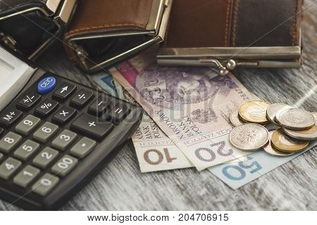 Polish Zloty With Little Wallets And Calculator On The Wooden Background