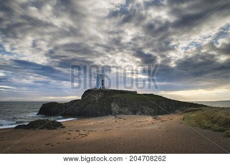Stunning Twr Mawr Lighthouse Landscape From Beach With Dramatic Sky And Cloud Formations