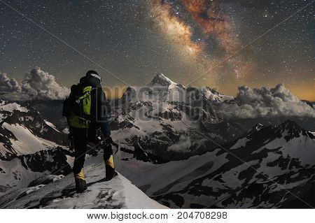 Night photo. Professional mountaineering guide fully equipped and with a backpack on his shoulders and an ice ax in his hands stands on top of the mountain in the snow and looks at the surrounding mountains over which the starry sky and the milky way. Ove