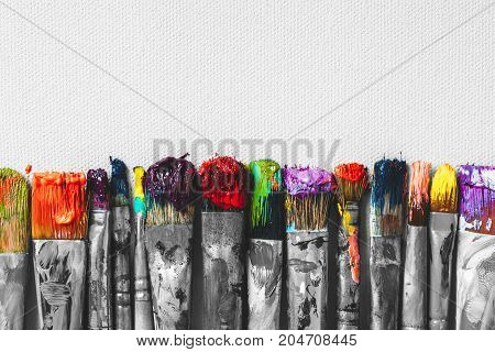 Row of artist paintbrushes with colorful bristle closeup on artistic canvas background retro black and white stylized.