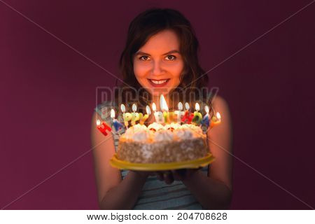 Portrait of pretty girl holding birthday cake at party
