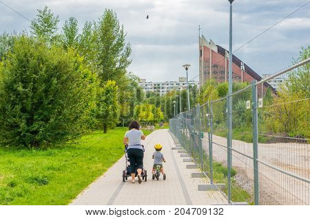 Woman with with baby buggy and toddler boy on a small bicycle on a footpath with metal barrier leading to a church on August 2017 in Poznan Poland