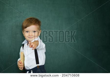 Cheerful Smiling Boy With Books On A Green Chalkboard Background
