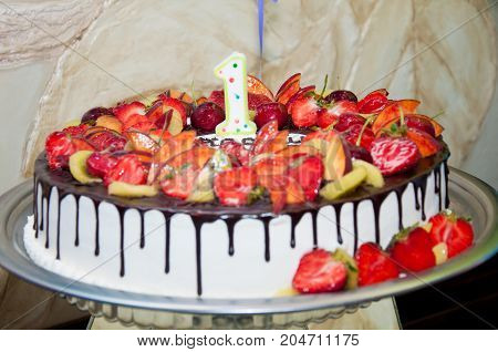 Party cake for first anniversary with chocolate glaze red strawberries cherry and number 1 on metal dish