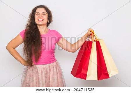 Portrait of young happy smiling woman with shopping bags, over white background. Purchase, sale and people concept.