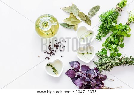 natural oil and fresh greenery for restaurant cooking with spices on white kitchen table background top view