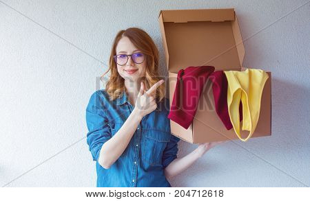 Woman In Jeans Shirt Standing On White Wall With Moving Box