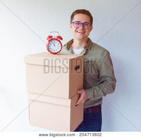 Handsome Man With Moving Boxes And Alarm Clock