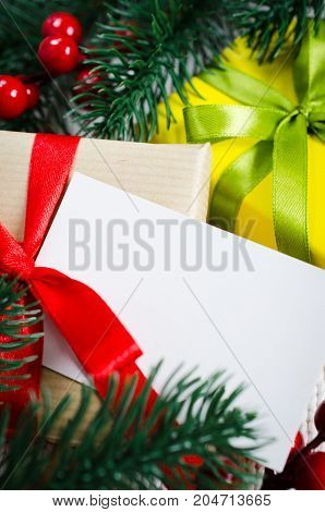 Christmas background with decorations and gift boxes on knitted board blanket. Xmas presents with blank postcard.