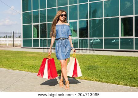 happiness, consumerism, sale and people concept - beautiful young woman with shopping bags