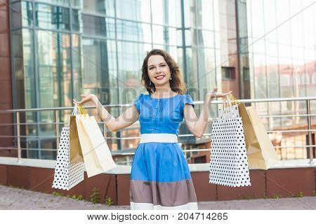 Beautiful girl with shopping bags is looking at camera and smiling on background the mall