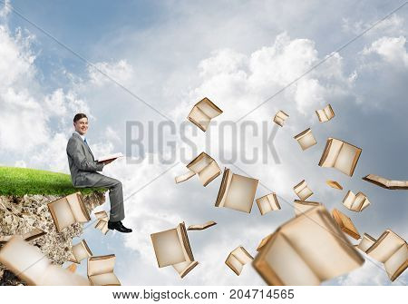 Young businessman floating on edge of a cliff with red book in hands