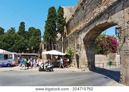 RHODES, GREECE - AUGUST 2017: Tourists are visiting souvenir shops near the old arch of Rhodes town fortress.