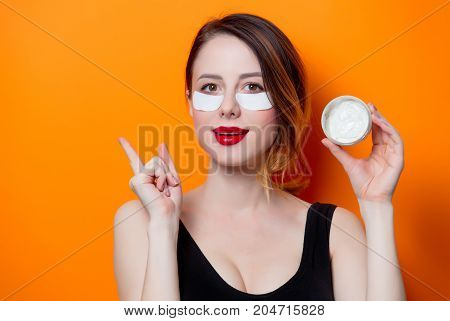 Woman Using Eye Patch For Her Eyes And Cream