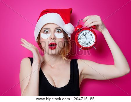 Woman Using Eye Patch For Her Eyes In Santa Claus Hat With Alarm Clock