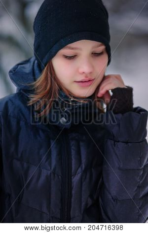 The girl looks down with a hand to her cheek. Warmly dressed child in winter on the street.