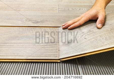 Laying laminate flooring in a flat the hands of master closeup