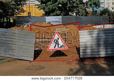 Road works sign hanging on a fence in the yard