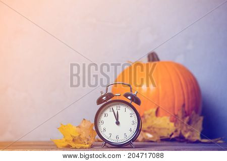 Retro Alarm Clock With Leaves With Pumpkin On Background.