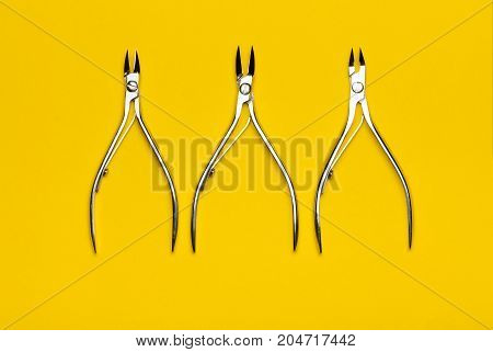 Tools of a manicure scissors on a yellow background