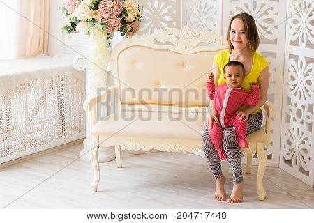 Loving Mother Holding Mixed Race Baby Son At Home.