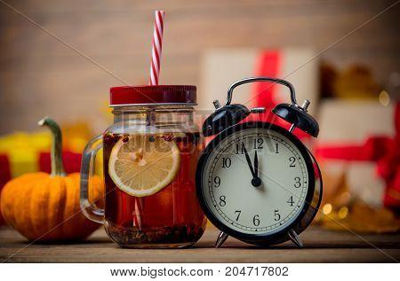 Tea And Alarm Clock Next To Pumpkin With Halloween Gift Box
