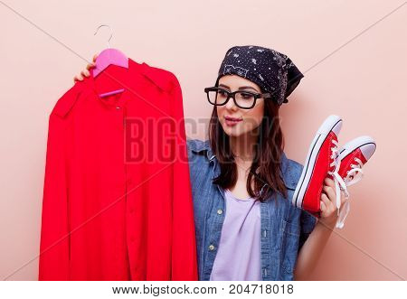 Young Redhead Girl Designer In Bandana Holding Hangers With Clothes
